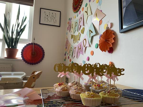 Photo of Fairy Cakes with icing on top and a stick with the word 'one' stuck to it. In the background you can see a happy birthday banner and some red paper fans.