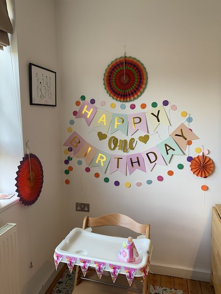 Birthday Decorations hung up in the flat including a sign saying 'Happy Birthday' and some red paper fans